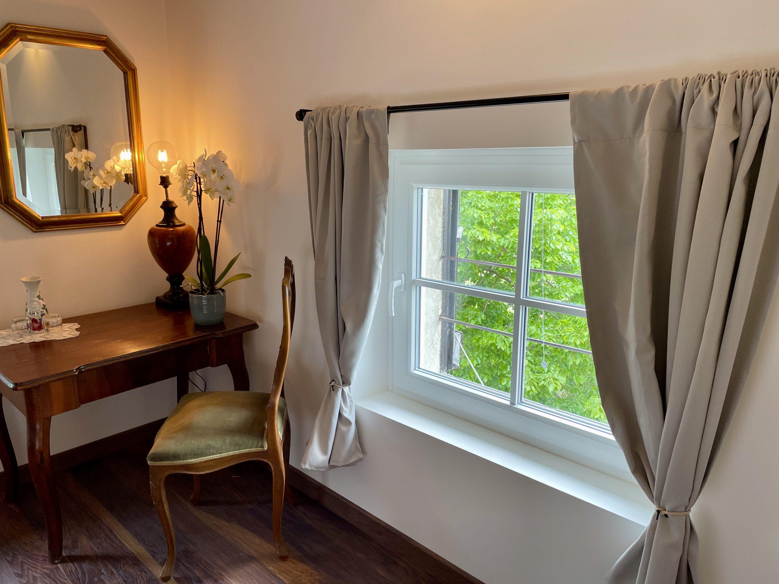 Tisch und Spiegel sowie aus Blick ins grüne im Zimmer Isola di Barbana